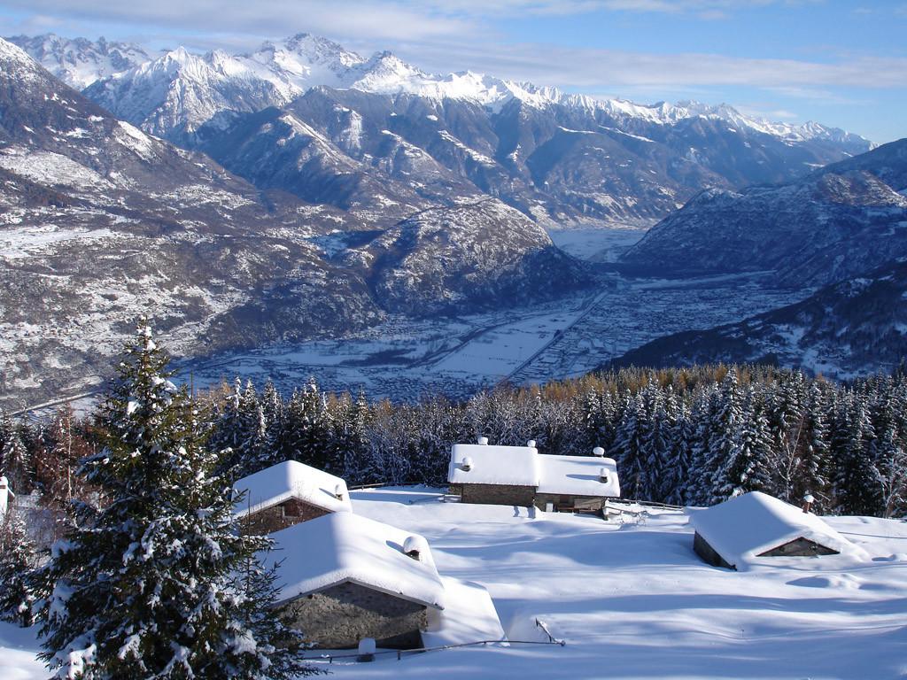 Le baite delle Tagliate 1450 m con il fondo Valle e le montagne della Val Masino.