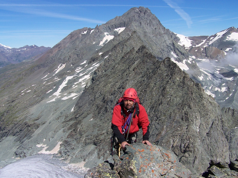 Jérôme sur l'arête, au fond la face Sud de la Bessanèse, en bas le glacier d'Arnès