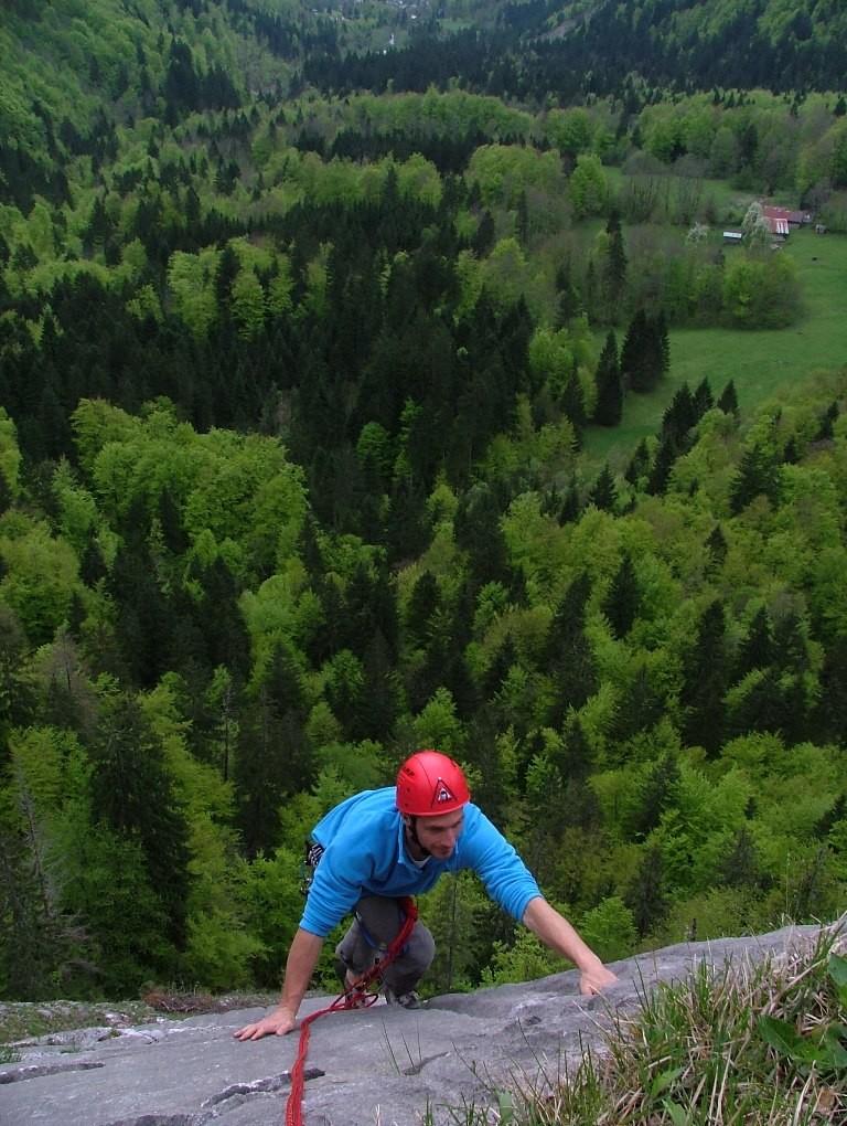 """Sylvain arrive au sommet de la 2° longueur du """"Vieux clou"""", en bas la clairière du Latay, au fond les Fontaines près de Samoëns"""