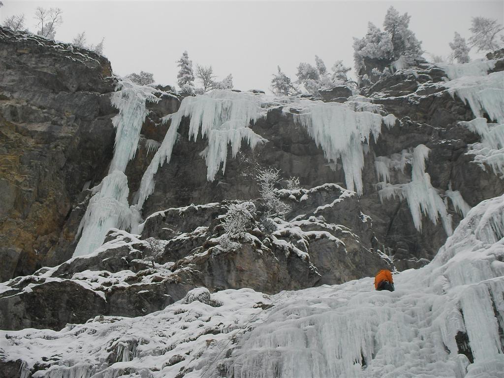 Un grimpeur dans la fin de L1 de Grimm et en haut à gauche la sortie de Reise (Kandersteg)