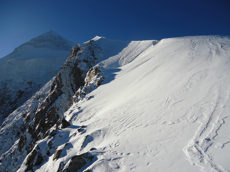 Fuori dalla cresta rocciosa, ci aspettano i lunghi pendii nevosi che portano all'anticima