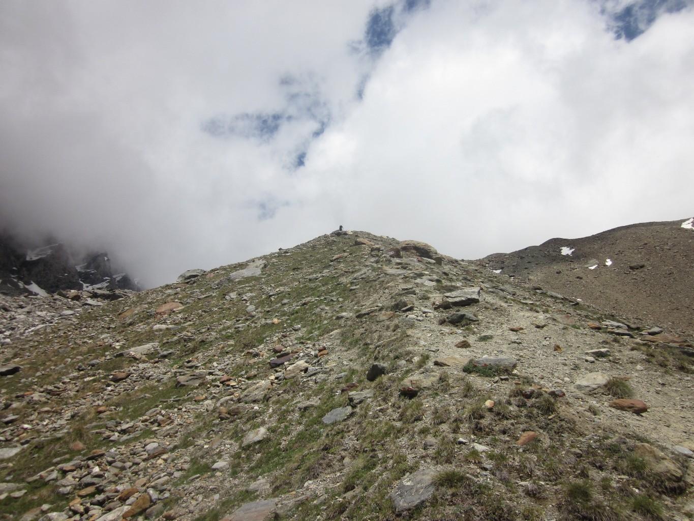 Un Tyrolien avec de minis skis monte au bivouac Mischabeljoch