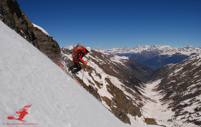 Roby durante la discesa dal Monte Aga vista sulla Val d'Ambria e sul gruppo del Bernina