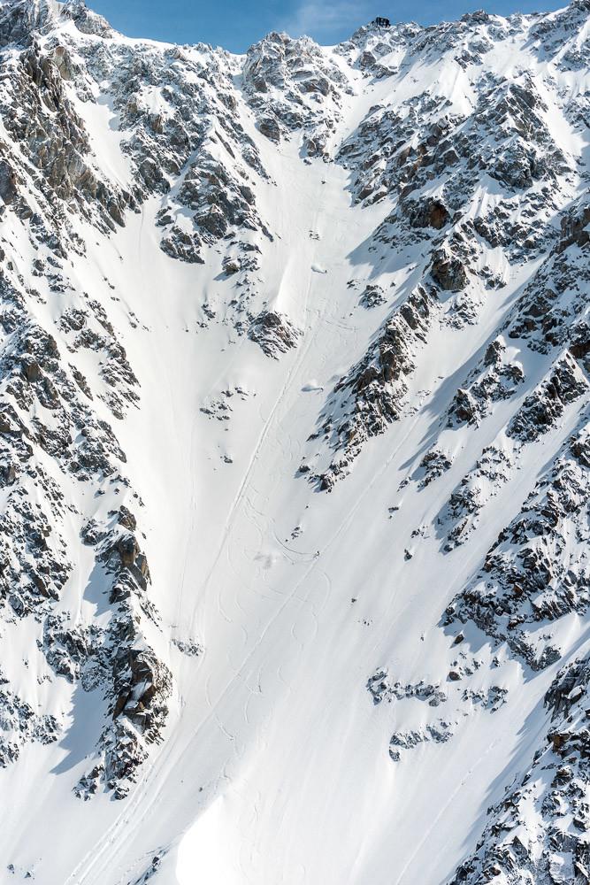 Plusieurs skieurs dans le Couloir des Cosmiques, le refuge et l'entrée du couloir bien visibles au dessus.